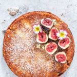Overhead view of a naked fig semolina cake. Fresh figs top the cake.