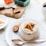 A small jar of fig overnight oats topped with fresh figs, resting on a white plate next to a spoon.