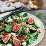 A fresh fig salad on a large white plate. Two glasses of wine rest in the background.