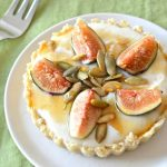 A fig tart on a white plate next to a fork.