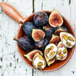 Overhead view of fresh figs with ricotta and pistachios in a dish.