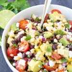 A white bowl filled with fresh corn salad.