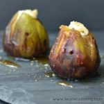 Two grilled figs stuffed with Brie cheese and drizzled with honey on a gray surface.