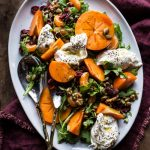 Overhead view of a cranberry persimmon salad on a white platter.