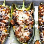 Healthy stuffed poblano peppers on a baking tray.
