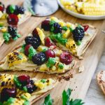 Sliced hummus flatbread with corn and berries on a wood serving board.