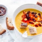 A bowl of sweet potato carrot soup with hunks of bread.
