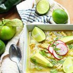Overhead view of a bowl of Mexican Chicken Pozole with limes.