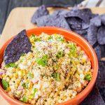 Mexican corn dip and a blue tortilla chip in an orange dip.