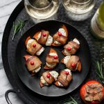 Overhead view of persimmon bacon bites on a gray plate, next to two glasses of wine.
