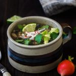 A mug of posole verde garnished with lime and cilantro. Radishes in the foreground.