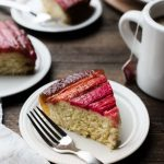 Rhubarb upside down cake on a white plate with a fork. Two more slices of cake rest on plates behind it, as does a coffee mug.