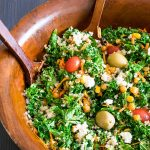 A wooden bowl full of roasted corn and chickpea salad with two wooden serving spoons.