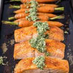 Salmon fillets and carrots on a sheet pan.