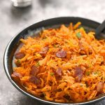 A gray dish of shredded carrots with bacon.