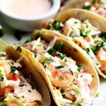 A plate of spicy shrimp tacos with a dish of sauce.