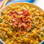 A large bowl of summer corn salad garnished with crumbled bacon.