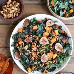 Kale salad topped with sweet potato cubes, halved figs and other veggies.