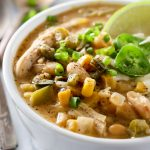 A bowl of white bean chicken chili garnished with jalapeno and lime wedge.
