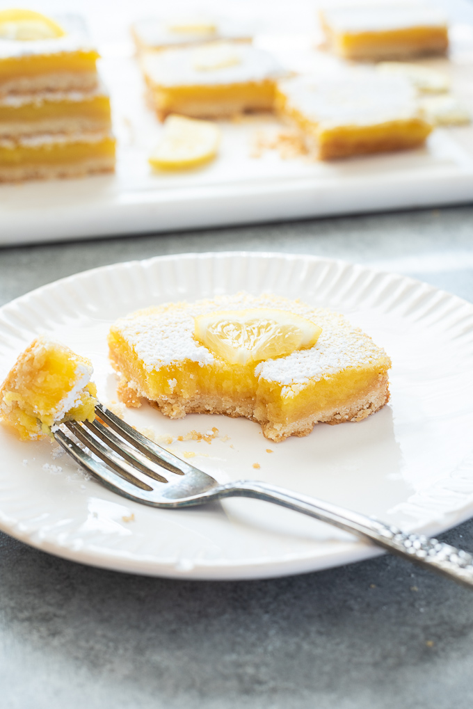 Lemon bar on a plate with bite taken out of it