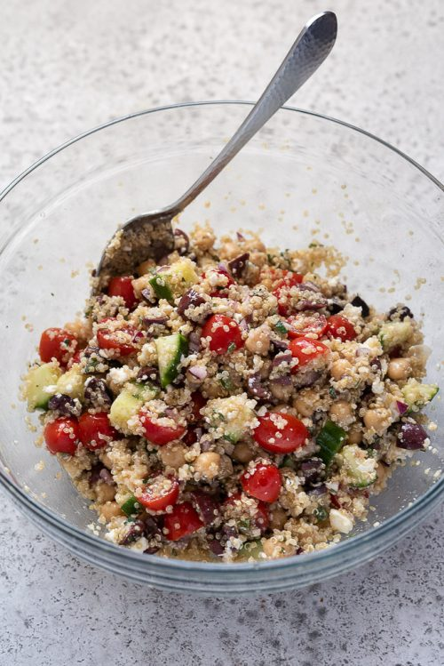 Greek quinoa salad in bowl with a spoon