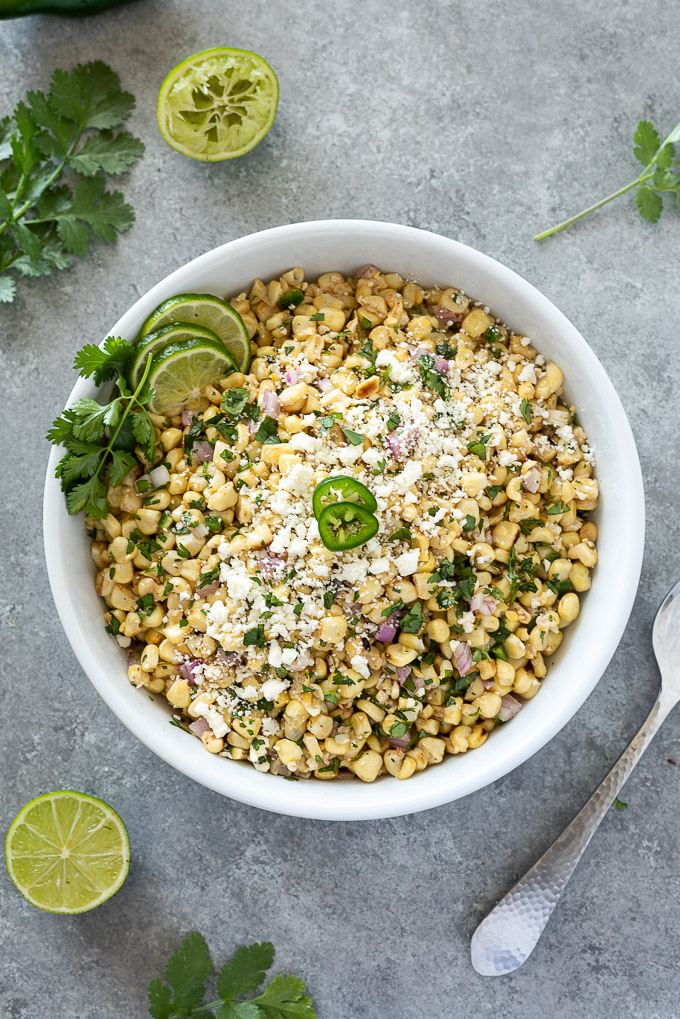 Mexican corn salad in a white bowl with lime and cilantro