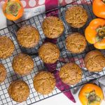 Overhead view of persimmon muffins on a wire cooling rack.