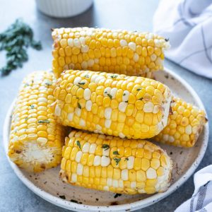 Air fryer corn on the cob piled on a white plate