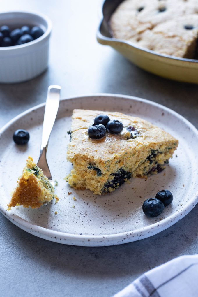 Slice of blueberry cornbread on plate with a fork