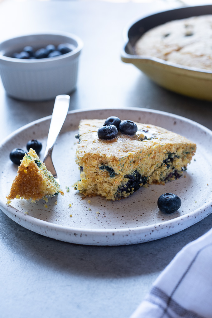 Wedge of blueberry cornbread on a plate with bite missing