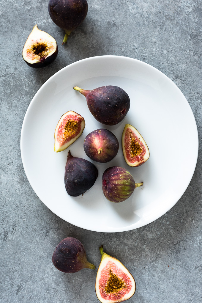 Whole and halved fresh figs on a white plate