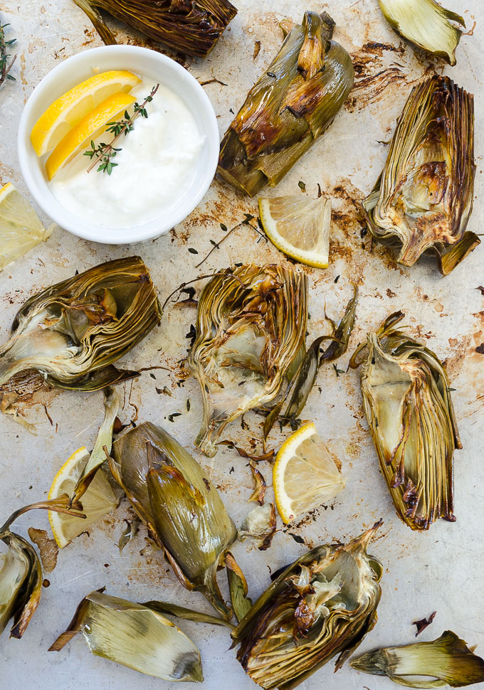 Oven roasted artichokes on a baking sheet with dip
