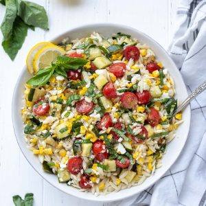 Lemon orzo pasta salad in a white bowl with basil on top
