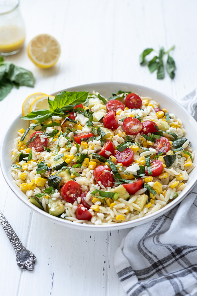 Orzo pasta salad in a bowl with linen alongside