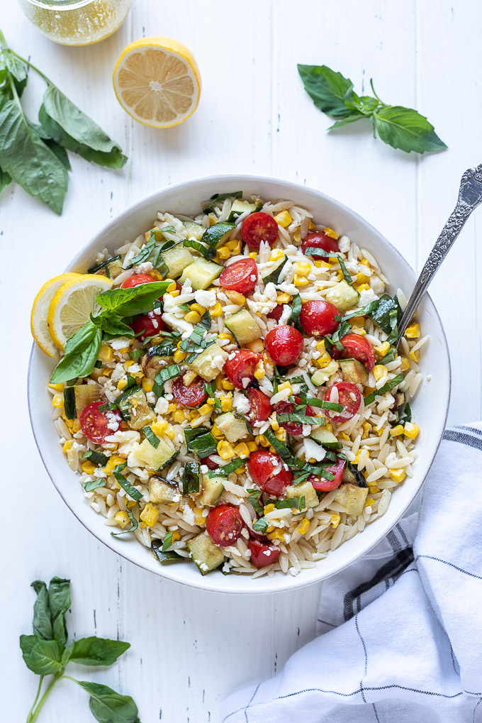Orzo pasta salad in a bowl with corn, cherry tomatoes and basil