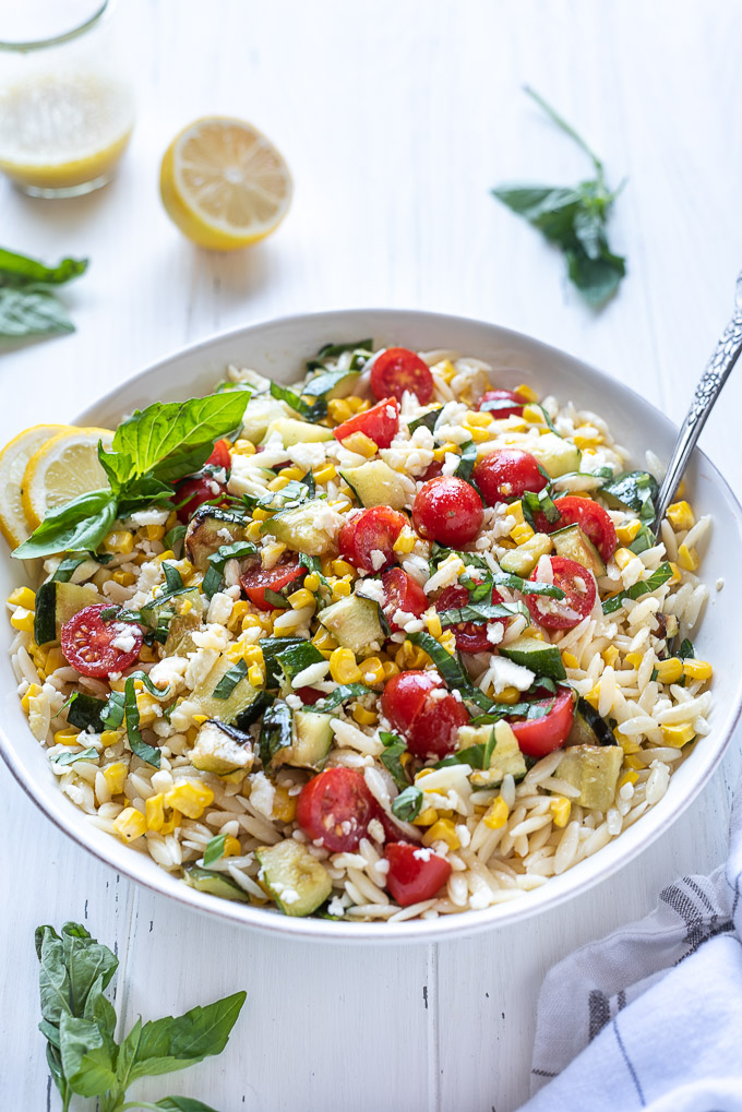 Summer orzo pasta salad in a bowl with a spoon nestled inside