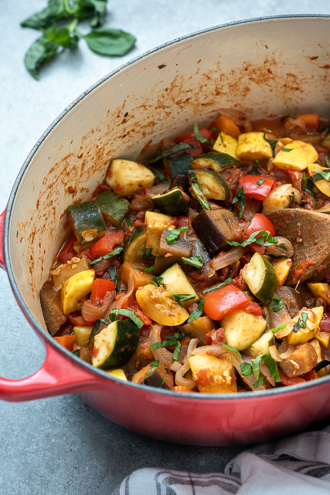 French ratatouille in a Dutch oven with a wooden spoon digging in