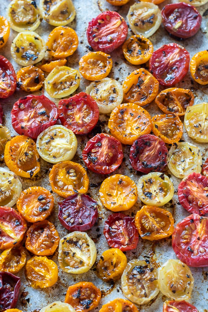 Roasted cherry tomatoes on a baking sheet with basil
