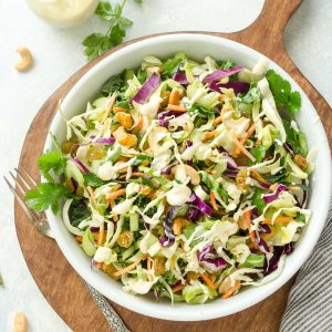 Bowl of vegan coleslaw on a wooden cutting board
