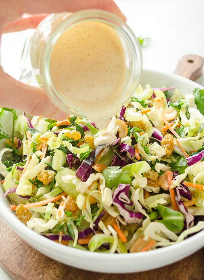 Vegan coleslaw dressing pouring over bowl of vegan coleslaw