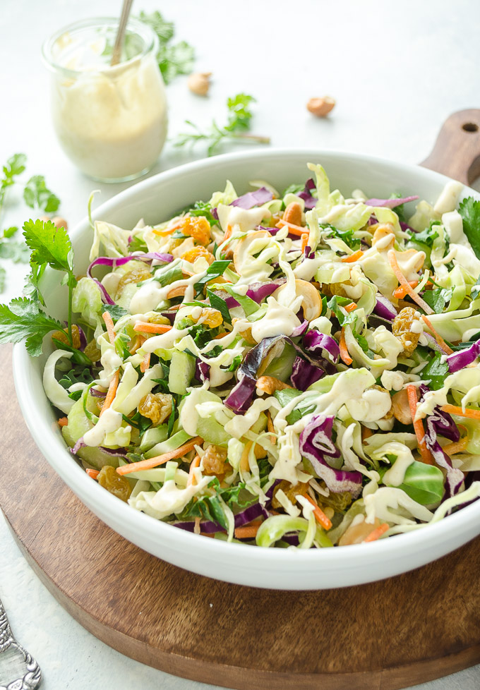 Vegan coleslaw in a white bowl with dressing in a jar