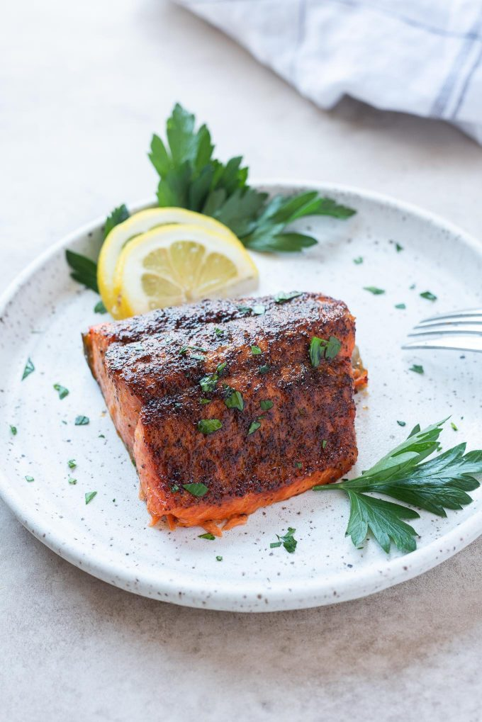 Air fryer salmon on a plate with lemon and parsley