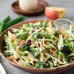 Broccoli slaw in a bowl with jar of dressing behind