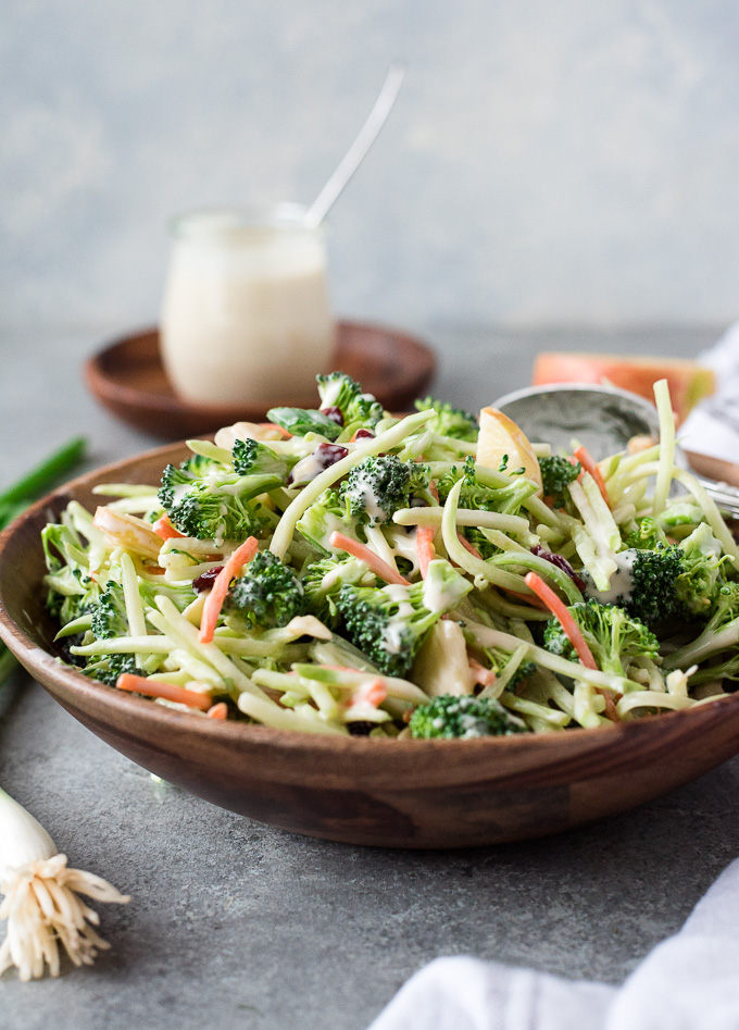 Bowl of broccoli slaw with serving spoon and coleslaw dressing nearby