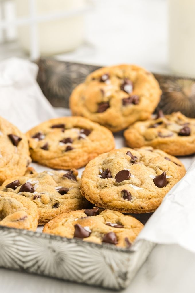 Thick and chewy chocolate chip cookies in a metal baking dish with parchment paper