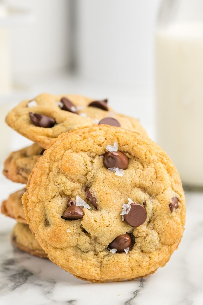 Stack of chocolate chip cookies with one cookie leaning against it