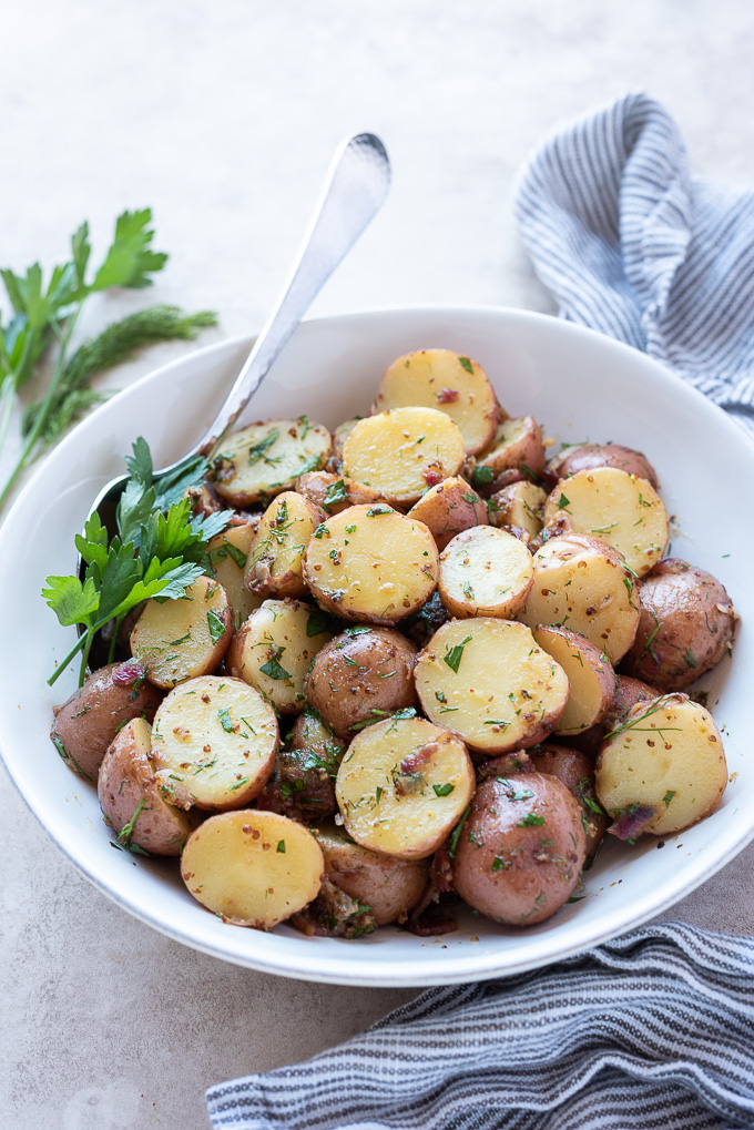 Warm german potato salad in a white bowl with a serving spoon