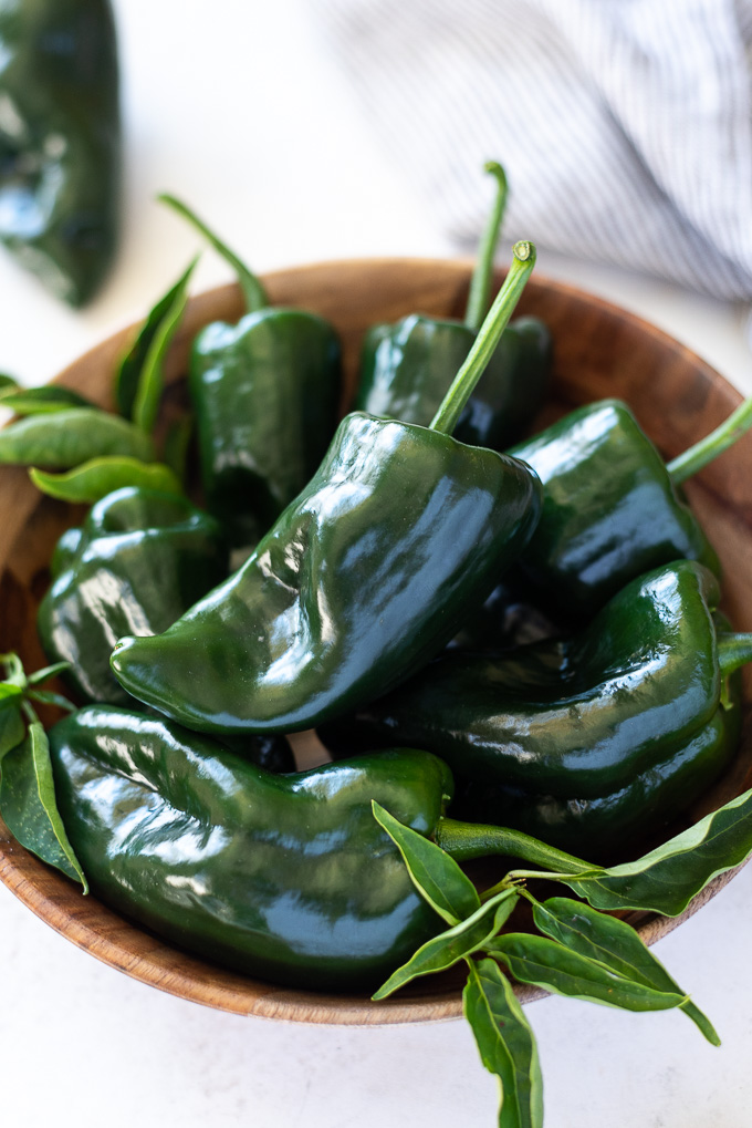 Teak bowl filled with poblano peppers with linen alongside