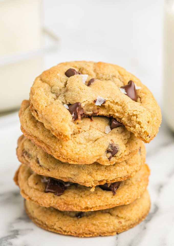 Stack of chewy chocolate chip cookies with bite out of top cookie