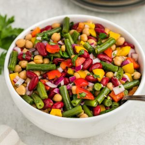 Three bean salad in white bowl with spoon inside
